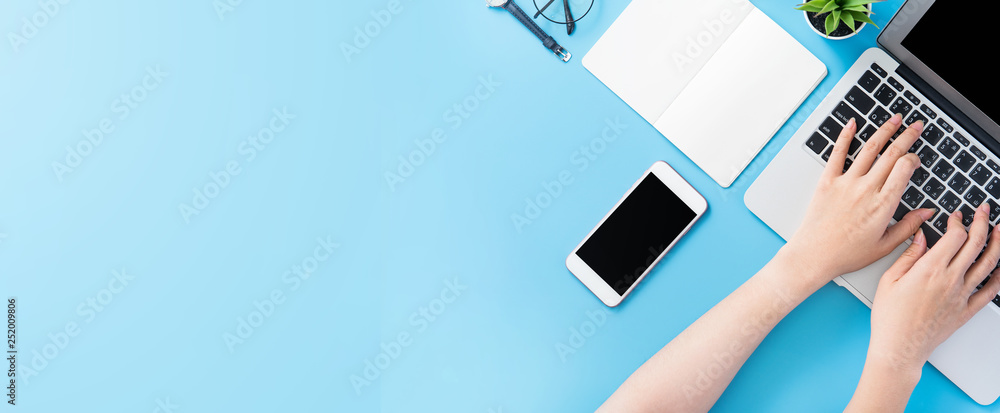 Fototapeta Asian student surf internet for job hunting. Freelancer blog writer typing isolated on a minimal clean blue desk concept, workspace, copy space, flat lay, top view, mock up