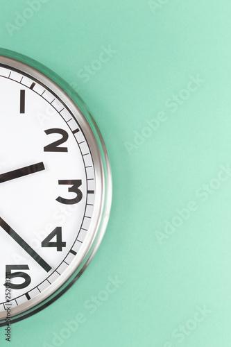 Valokuva  Part of analogue plain wall clock on trendy mint background