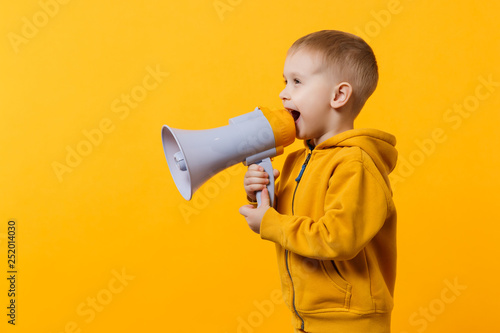 Little fun kid boy 3-4 years old in yellow clothes holding, speaking in electronic megaphone isolated on orange wall background, children studio portrait. People childhood concept. Mock up copy space.