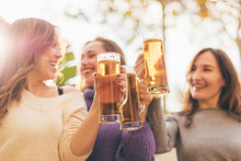Three Happy Smiling Women Drinking Beer And Having Fun Together - Female Friendship, Celebration Concept - Focus On Glasses Of Beer
