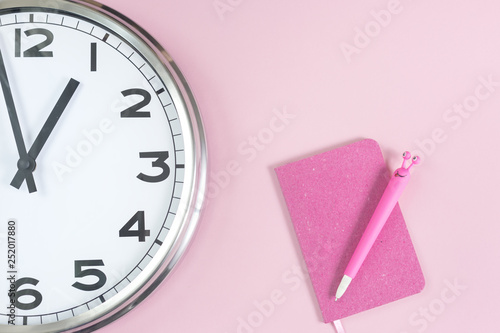 Foto  Part of analogue plain wall clock with trendy feminine pink notepad and a funny pen