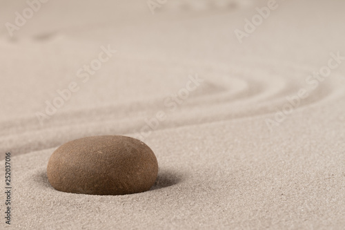 Fotobehang Stenen in het Zand Concentration trough focus on a zen meditation stone. Round rock in sand texture background. Concept for yoga or spa welness treatment.