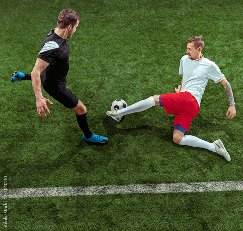 Tuinposter Voetbal Football player tackling for ball over green grass background. Professional male soccer players in motion at stadium. Fit jumping men in action, jump, movement at game.