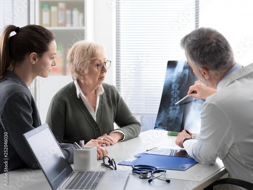 Valokuvatapetti Doctor checking a senior patient's x-ray image