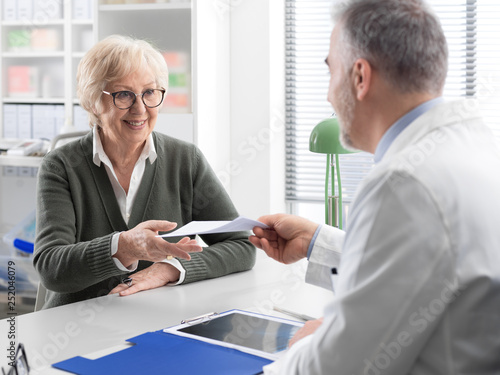 Photo Professional doctor giving a prescription to a senior patient
