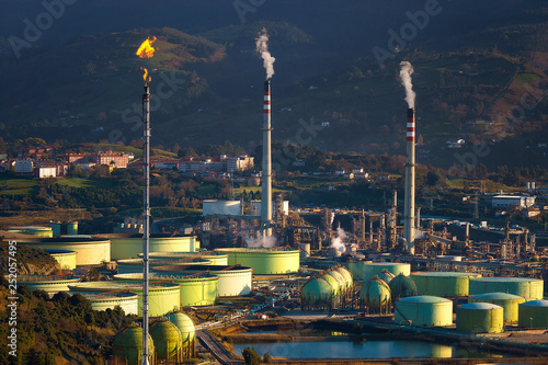 Foto industrial refinery and storage tanks with smokestack and smoke