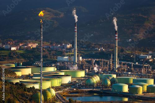 Fotografie, Obraz  industrial refinery and storage tanks with smokestack and smoke