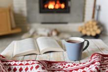 Book And Cup Of Tea Near Burni...