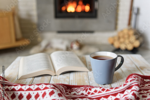 Photo Book and cup of tea near burning fireplace. Hygge concept