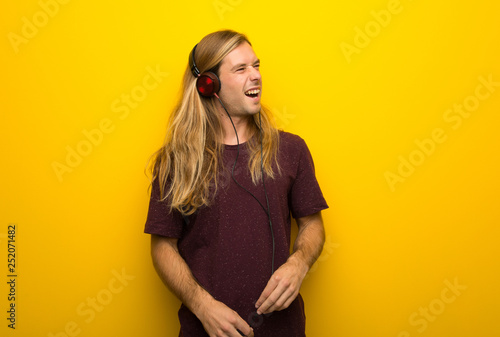 Blond man with long hair over yellow wall listening to music with headphones - 252071482