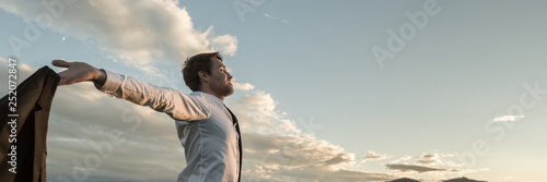 Businessman embracing life standing under cloudy sky Fototapeta
