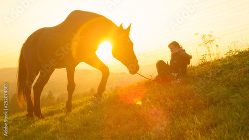 Fotografía SILHOUETTE: Big stallion grazing at sunset while girl sits nearby in the grass