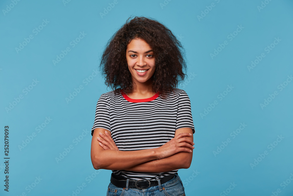 Fototapety, obrazy: Self-confident happy young African American woman with long curly dark hair laughing smiling against blue background standing with arms crossed
