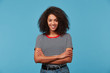Self-confident happy young African American woman with long curly dark hair laughing smiling against blue background standing with arms crossed