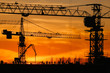 Cranes silhouettes in warm sunset lights with builders working on the roof