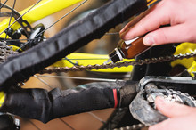 Close-up Of Men's Hands Led By Masters Grease With Special Grease Bicycle Chain Of Mountain Bike In The Home Workshop