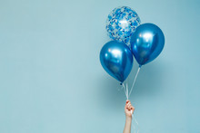 Bright Matte Balloons On A Blue Background.  Three Blue Inflated Balloons. Stylish Party With Balloons. Round Blue And Transparent  Balloon. Hand Hold  Balloon Isolated