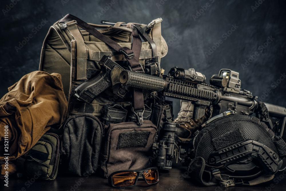 Fototapeta Military uniform and equipment. Body armor, gun, assault rifle, helmet, night vision goggles. Studio photo against a dark textured wall