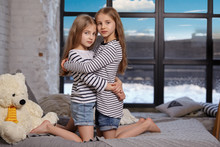 The Image Of Two Little Sisters Sitting On The Bed In The Room.