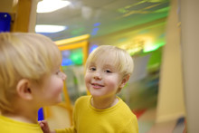 Cute Little Boy Looks In Distorting Mirror In Playcenter.