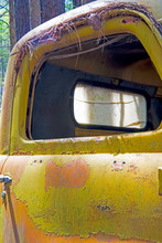 Peeling Yellow Paint On An Old Rustic Truck At The Junkyard.