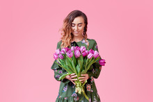 Cheerful Young Redhead  Lady In Fashionable Green Dress Being Excited To Get Bouquet Of Spring Yellow Flowers Tulips On Women's Day Isolated Over Pink Background.