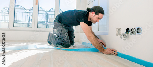 Workers in a flat work on a floor. glue edge insulation strip. balance the floor.