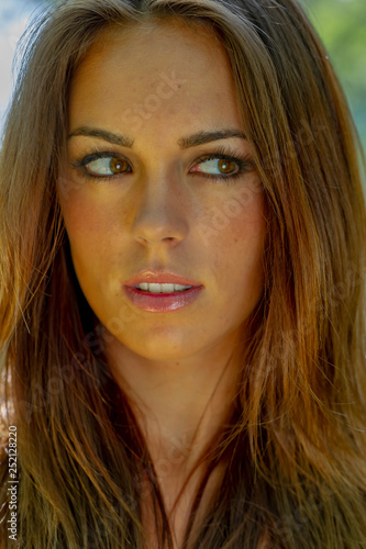 Valokuva  Headshot Of A Beautiful Brunette Model Poses In An Outdoor Environment