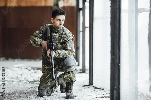 Photo  A young military soldier sits with a big rifle in his hands, near the window of