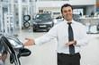 Professional car salesman working at the dealership salon