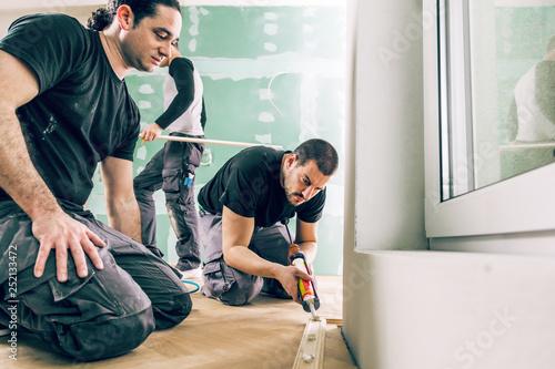 Mann mit der Kleberspritze befestigt die Sockelleiste an einer Baustelle Canvas Print