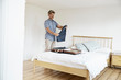 Mature man packing suitcase in bedroom