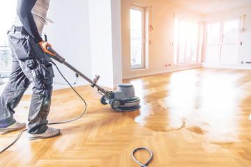 Varnishing of oak parquet floor, workers  tool.