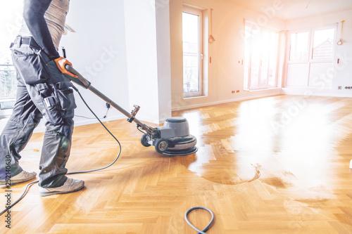 Obraz Varnishing of oak parquet floor, workers  tool. - fototapety do salonu
