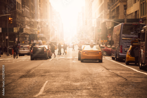 Fotografiet  Defocused blur along busy New York City street in midtown Manhattan with cars an
