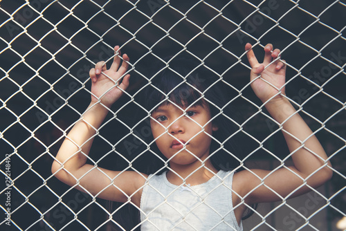 Photo sad Asian girl child alone in cage was imprisoned make no freedom or lack of fr