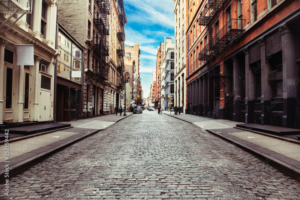 Fototapeta New York City old SoHo Downtown paving stone street with retail stores and luxury apartments