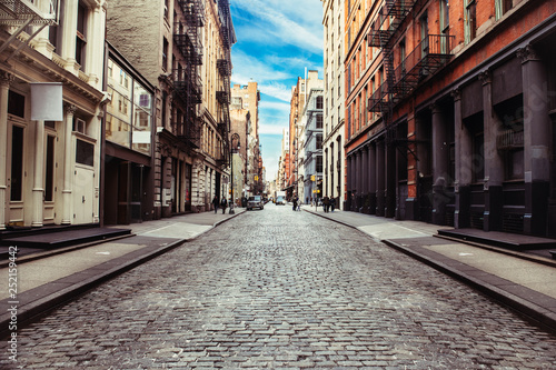 New York City old SoHo Downtown paving stone street with retail stores and luxury apartments - 252159442