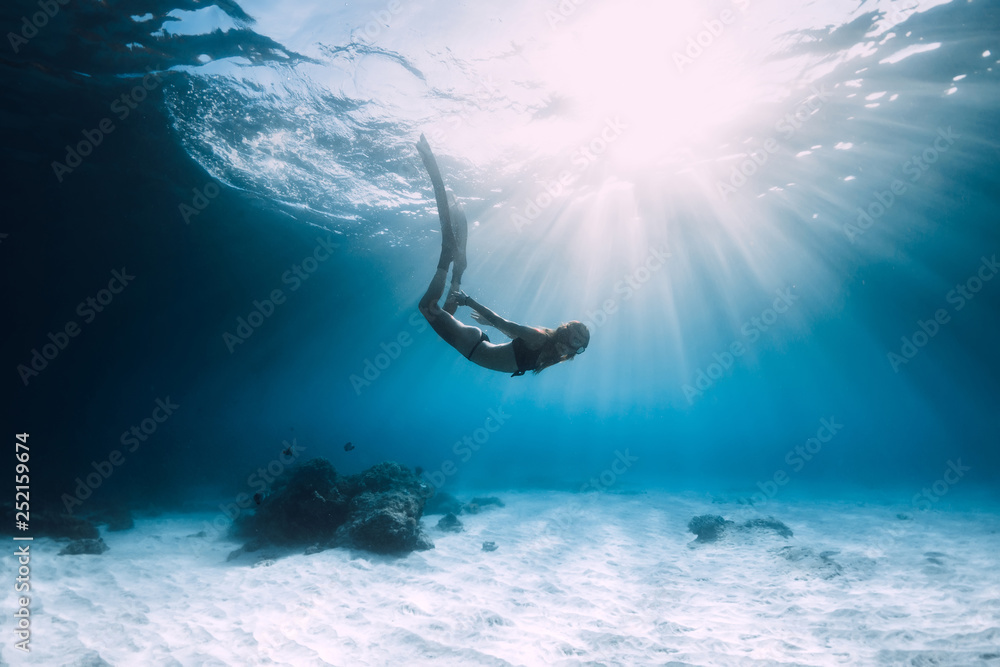 Fototapety, obrazy: Woman freediver dive over sandy sea with fins. Freediving in blue ocean
