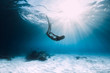 Woman freediver dive over sandy sea with fins. Freediving in blue ocean
