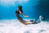 Woman freediver swim over sandy sea with fins. Freediving underwater in blue ocean