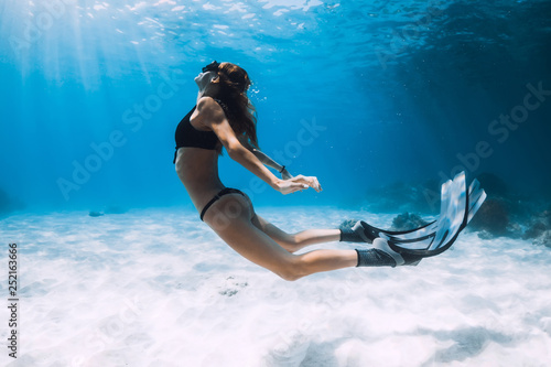 Foto  Woman freediver swim over sandy sea with fins