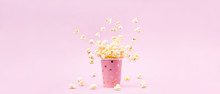 Flying Popcorn In A Bright Glass And On A Pink Background.