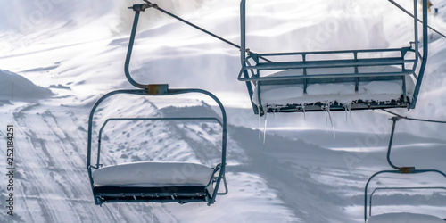 Empty ski lifts with sunlit snow in the background Wallpaper Mural