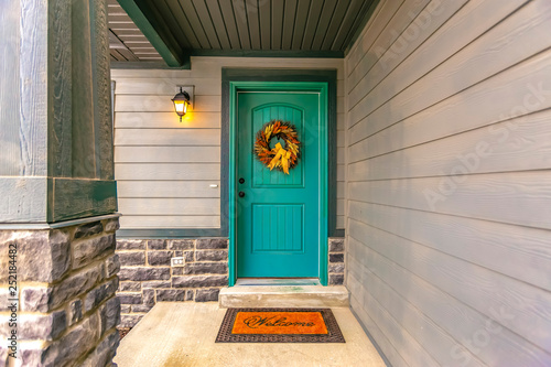 Obraz Entryway with wreath and doormat on the front door - fototapety do salonu