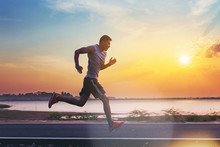Silhouette Of Man Running Sprinting On Road. Fit Male Fitness Runner During Outdoor Workout With Sunset Background