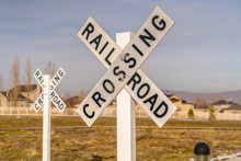 Railroad Crossing Signs Against Homes And Sky