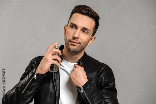 Fotografia  Handsome man with bottle of perfume on grey background