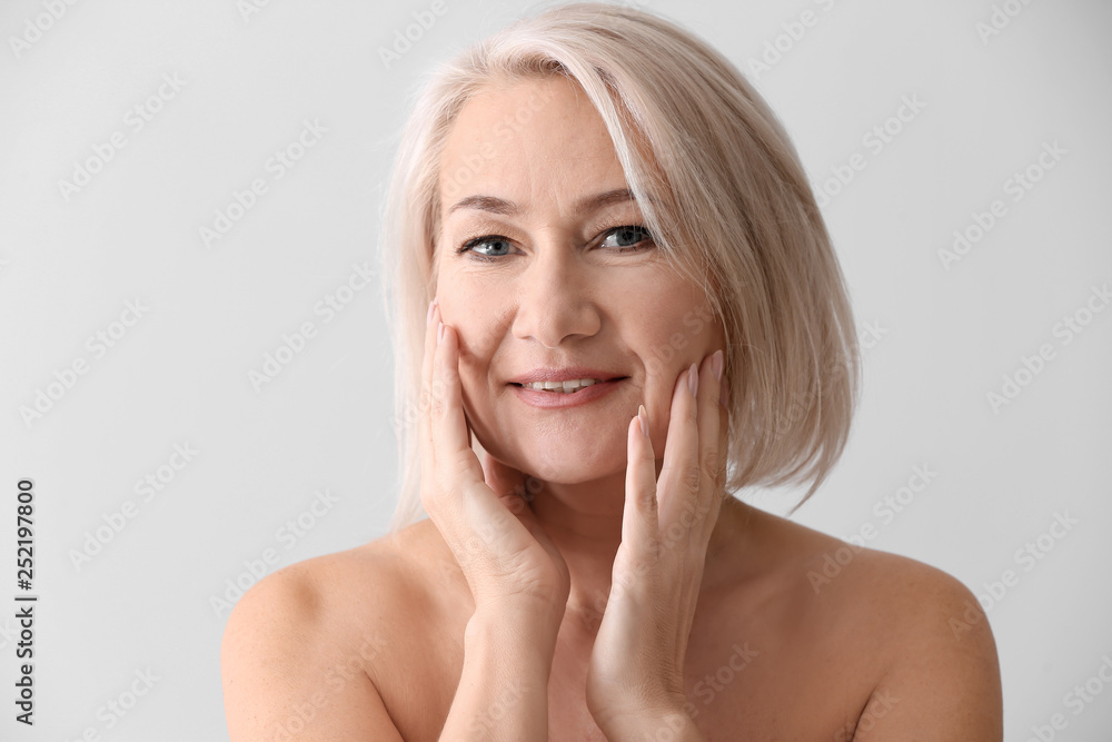 Fototapety, obrazy: Mature woman giving herself face massage on light background