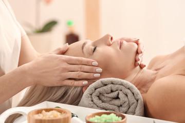 Obraz na płótnie Canvas Mature woman receiving face massage in beauty salon
